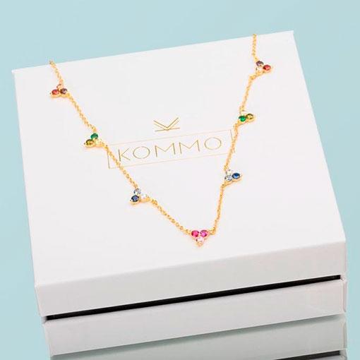 collar atenea gold de la marca kommo puesto encima de la caja de la marca