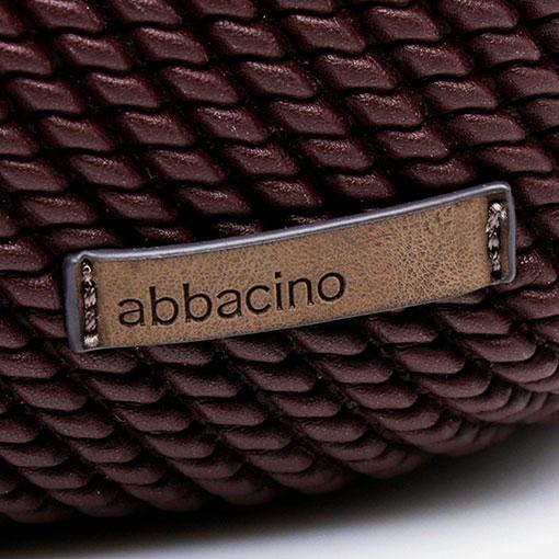 detalle de mochila acolchada de la marca abaccino con logotipo en la parte delantera color granate